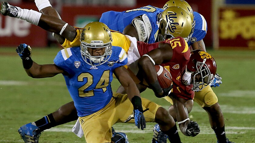 Ishmael Adams (24), Randall Goforth (background) and Myles Jack (30) bring down USC receiver Nelson Agholor during the 2013 rivalry game.