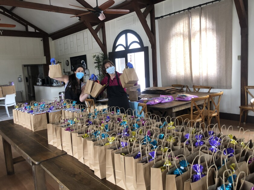 Following current coronavirus safety protocols, church members prepare Easter bags for parishoners.
