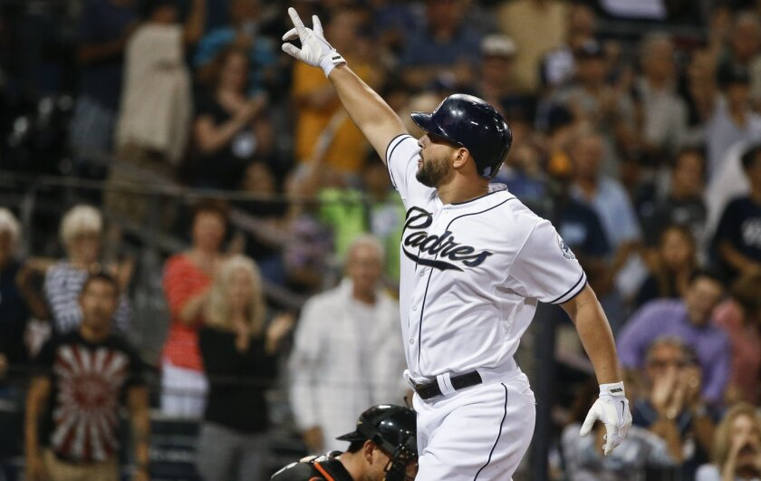 San Diego Padres' Yonder Alonso signals to someone in the crowd as he crosses homes plate with his home run against the Miami Marlins during the fifth inning of a baseball game Friday, July 24, 2015, in San Diego. (AP Photo/Lenny Ignelzi)