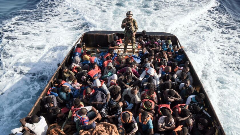 A member of the Libyan coast guard watches over a boat of rescued migrants who were trying to reach Europe on June 27, 2017.