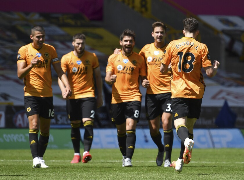 Wolverhampton Wanderers' Diogo Jota, front right, celebrates with teammates after scoring his side's third goal during the English Premier League soccer match between Watford and Everton at the Molineux Stadium in Wolverhampton, England, Sunday, July 12, 2020. (Ben Stansall/Pool via AP)