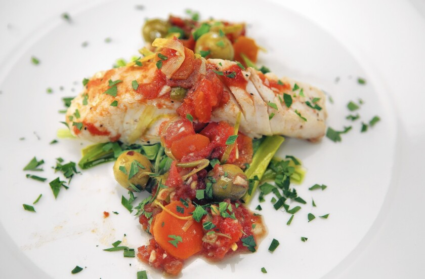 Fish dishes are a traditional part of Rosh Hashanah. Here, halibut with leeks, tomatoes and olives.