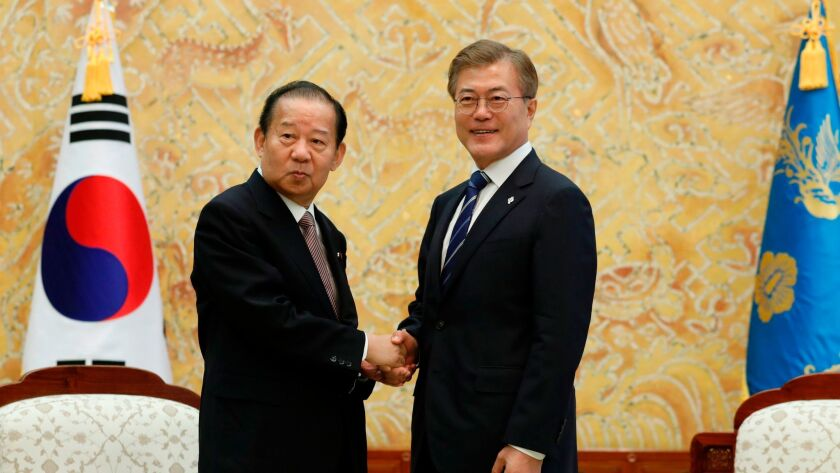 South Korean President Moon Jae-in shakes hands with Toshihiro Nikai, secretary general of the Japanese Liberal Democratic Party, during their meeting at the Presidential Blue House in Seoul on June 12.