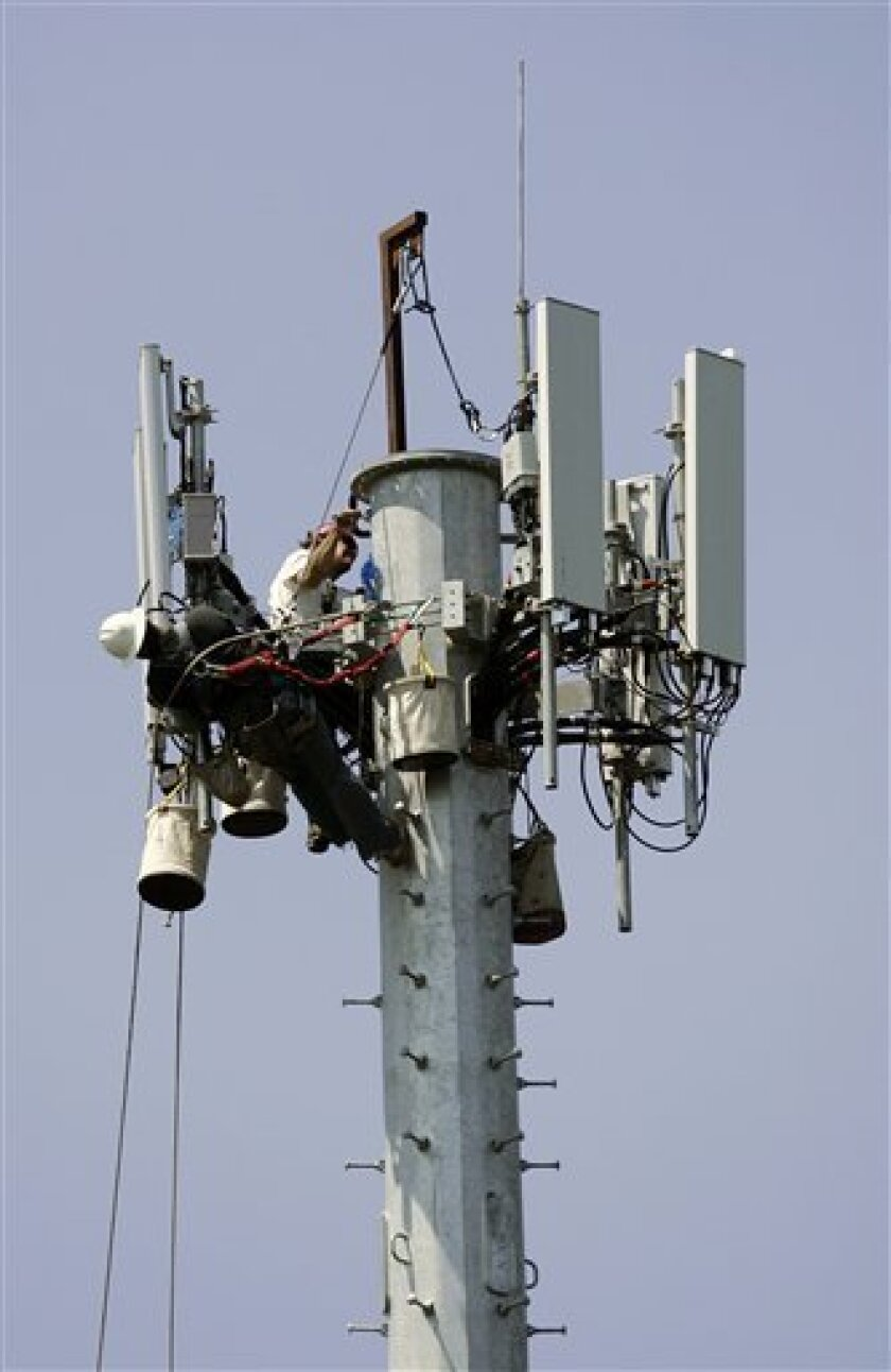 In this file photo taken July 16, 2008, workers are seen at the construction of a cellular telephone antenna tower in Lakewood, N.J.. A Long Island township has imposed restrictions on the placement of new cell towers that are among the toughest in the country, and one phone company said, Thursday,