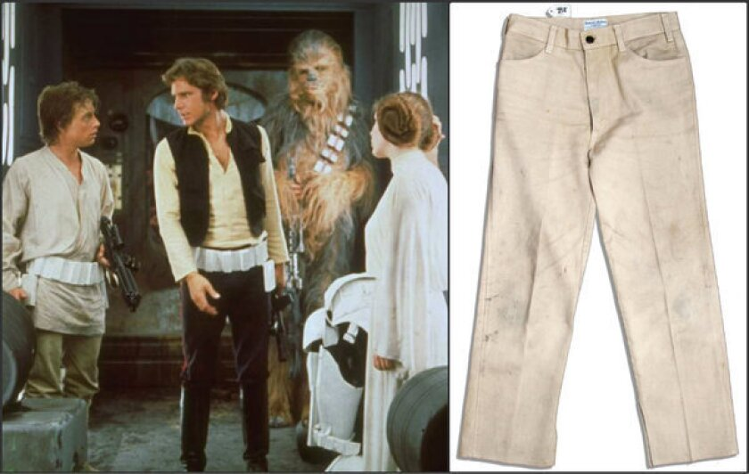 """Mark Hamill, left, Harrison Ford, Peter Mayhew and Carrie Fisher in a scene from """"Star Wars."""" At right, a pair of pants, worn by Hamill in the 1977 film, is up for auction."""