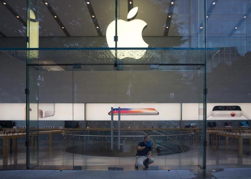 Fotografía de archivo del 3 de noviembre de 2017 de un hombre limpiando el interior de las ventanas de una tienda Apple. EFE/Archivo