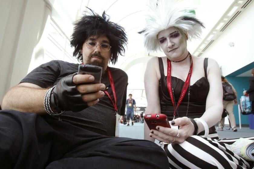 Rodney Warren and Ramona Creel dressed as Guy Lydia and Chick Beetlejuice check their phones at Comic-Con. (K.C. Alfred / UT San Diego)
