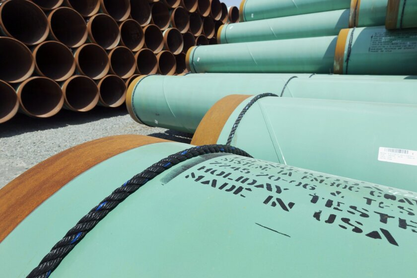 FILE - This May 24, 2012 file photo shows some of about 500 miles worth of coated steel pipe manufactured by Welspun Pipes, Inc., originally for the Keystone oil pipeline, stored in Little Rock, Ark. The US is extending indefinitely the amount of time federal agencies have to review the Keystone XL pipeline, the State Department said Friday, likely punting the decision over the controversial oil pipeline until after the midterm elections. The State Department didn't say how much longer it will grant agencies to weigh in, but cited a recent decision by a Nebraska judge that overturned a state law that allowed the pipeline's path through the state, prompting uncertainty and an ongoing legal battle. Nebraska's Supreme Court isn't expected to rule for another several months and there could be more legal maneuvering after that, potentially freeing President Barack Obama to avoid making a final call on the pipeline until after the election in November. (AP Photo/Danny Johnston, File)