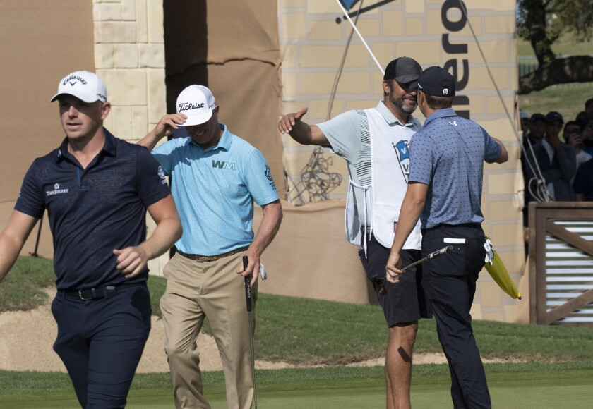 Jordan Spieth, right, gives his caddie, Michael Geller, center right, a hug after winning the Valero Texas Open golf tournament in San Antonio, Sunday, April 4, 2021. Spieth defeated Matt Wallace, far left, and Charley Hoffman, second from left. (AP Photo/Michael Thomas)