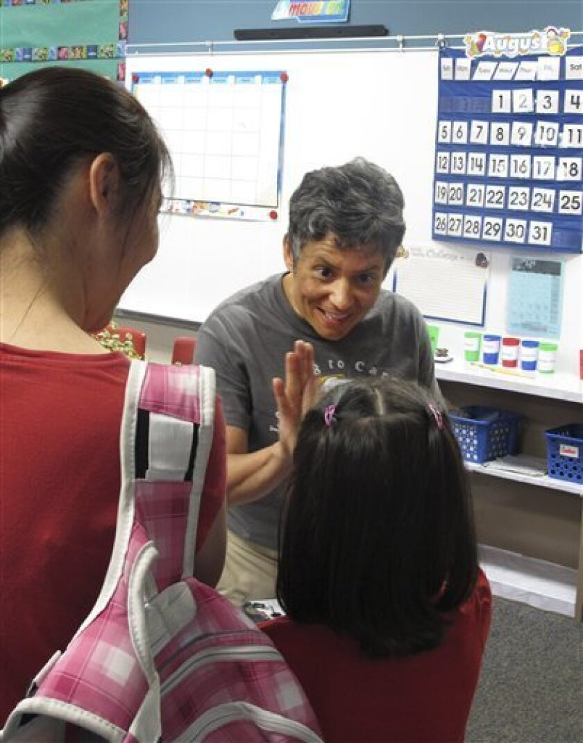 In this photo taken Aug. 20, 2012, teacher Tammy Schmidt high-fives one of her new students at Ridgewood Elementary School in Hilliard, Ohio. Schmidt is among nearly 109,000 Ohio teachers who will fall under new evaluation criteria starting next summer. (AP Photo/Kantele Franko)