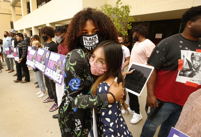 Tianna Arata, left, hugs girlfriend Nicole Huffman before the rally on Tuesday.
