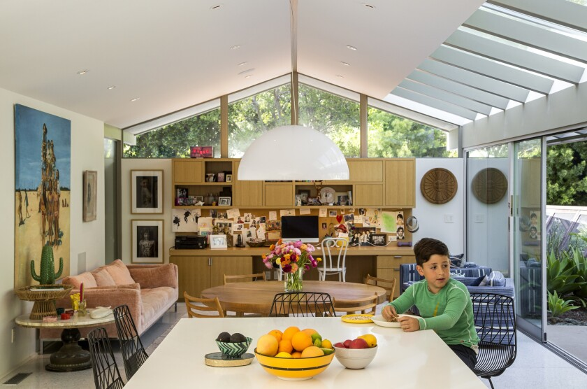 Architect John Bertram transformed a 1963 home by Pasadena-based architects Smith & Williams for a family of four. Here, 10-year-old Harry has lunch in the new kitchen, which was moved from the front of the house to the back.