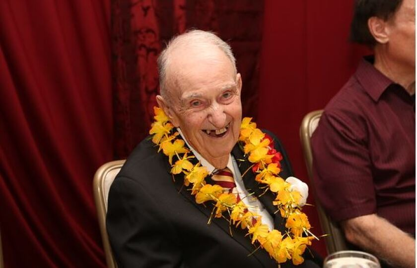 Dennis Murphy wearing a lei with a business suit