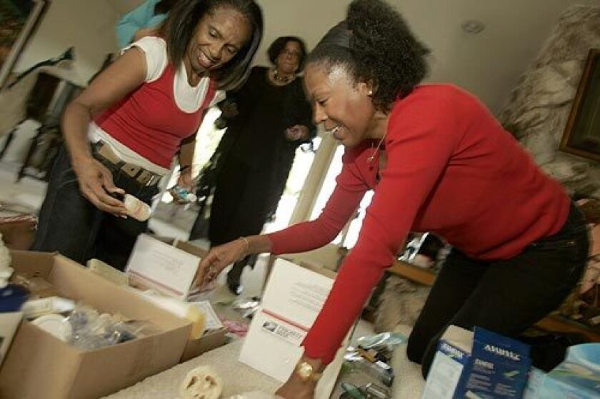 """Shirley Harris, left, and Myraline Morris Whitaker fix up care packages to send to female African American soldiers in Iraq. Their Sisterfriends book club """"adopted"""" the soldiers after Morris Whitaker got wind of the issues they face. """"We want to give them nourishment for the soul, as well as for their hair,"""" said Morris Whitaker."""