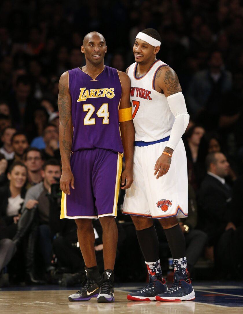 Los Angeles Lakers forward Kobe Bryant (24) chats with New York Knicks forward Carmelo Anthony (7) during a lull in play in the second half of an NBA basketball game at Madison Square Garden in New York, Sunday, Nov. 8, 2015.  The Knicks defeated the Lakers 99-95. (AP Photo/Kathy Willens)
