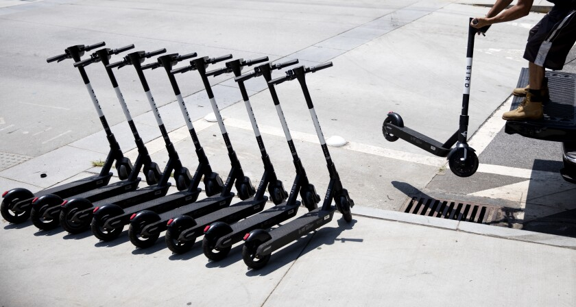 A person lines up electric scooters on a street corner