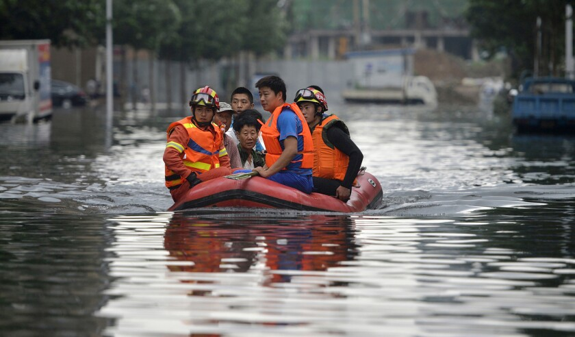 Rescuers transport people along a flooded street in Shenyang in northeastern China's Liaoning Province.