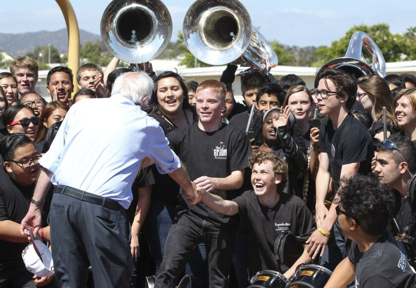 After speaking to a crowd of thousands at his campaign rally in the Rancho Buena Vista High School football stadium in Vista on Sunday, Democratic presidential candidate Bernie Sanders shakes hands with members of the school's marching band, called Rhythm of the Ranch, after posing for a picture wi
