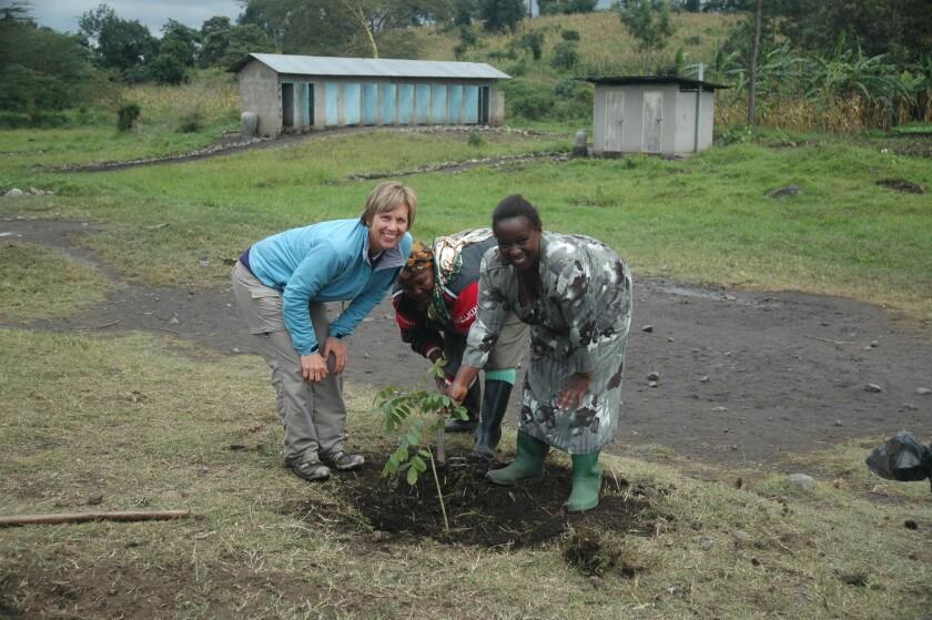Cindy Outlaw planting a tree at the school in Siha, Tanzania.