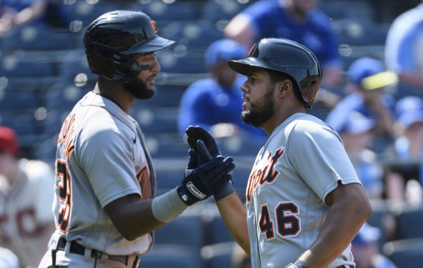 The Detroit Tigers' Jeimer Candelario, right, is congratulated by teammate Niko Goodrum, left, after scoring against the Kansas City Royals during the ninth inning of a baseball game in Kansas City, Mo., Wednesday, June 16, 2021. (AP Photo/Reed Hoffmann)