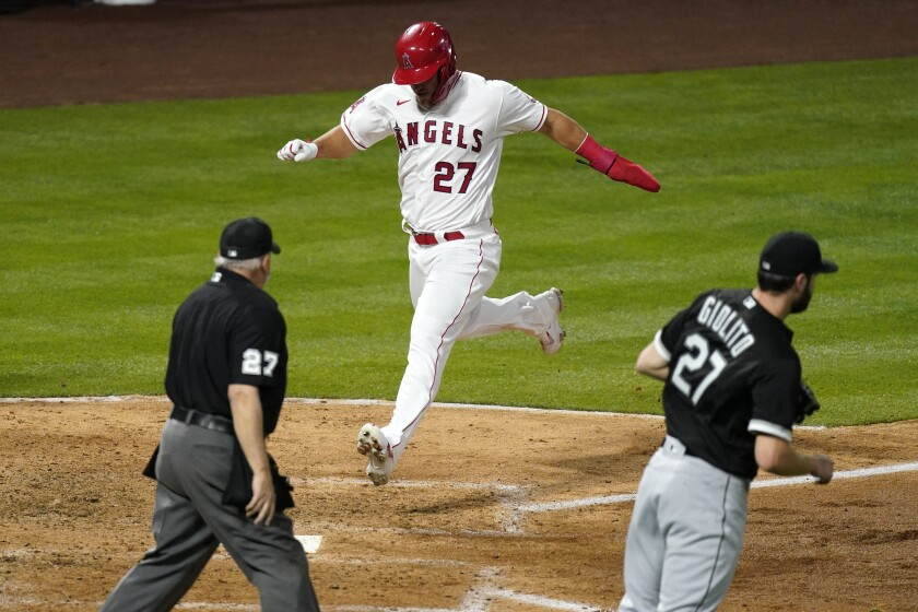 Los Angeles Angels' Mike Trout, center, scores on a single by Justin Upton as Chicago White Sox starting pitcher Lucas Giolito, right, covers the plate and home plate umpire Larry Vanover watches during the fourth inning of an Opening Day baseball game Thursday, April 1, 2021, in Anaheim, Calif. (AP Photo/Mark J. Terrill)