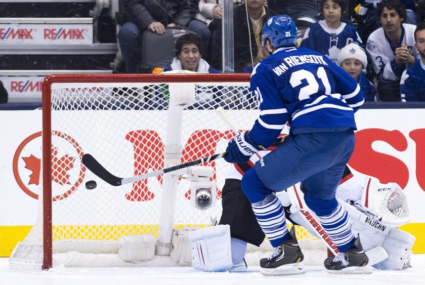 Toronto Maple Leafs Forward James van Riemsdyk (21) scores past New Jersey Devils goalie Cory Schneider to defeat the devils in a shoot out during a NHL hockey game in Toronto on Sunday, Jan. 12, 2014. (AP Photo/The Canadian Press, Nathan Denette)