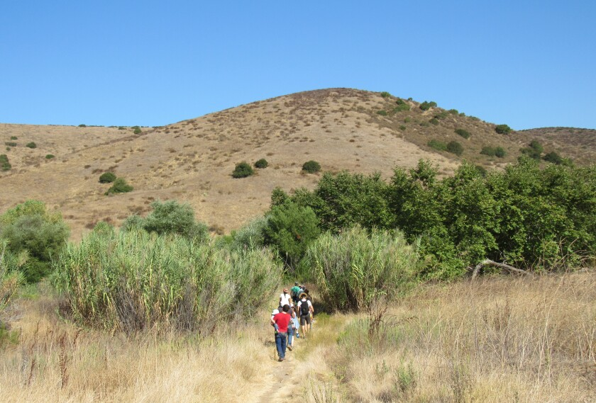 Hikers move near the Stowe Trail on property belonging to HomeFed, which hopes to build about 3,000 homes in Santee.