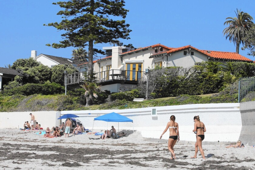 Beachgoers enjoy a sunny day in front of Mitt Romney's La Jolla home in 2012. Renovation of the $12-million residence began last spring and is expected to wrap up before the end of the year.