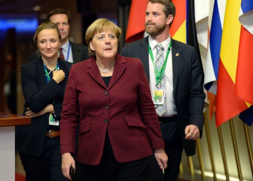 German Chancellor Angela Merkel, center, departs the European Union summit in Brussels.
