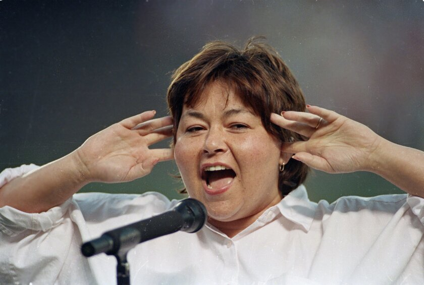 Comedienne Roseanne Barr holds her fingers in her ears as she screams the National Anthem between games of the San Diego Padres and the Cincinnati Reds doubleheader on July 25, 1990 in San Diego, Calif. She was booed loudly and she made an obscene gesture and spat when she was finished.