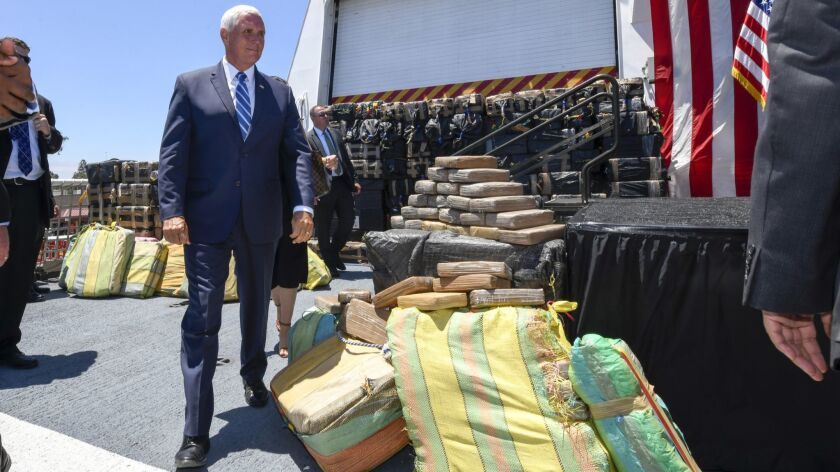 Vice President Mike Pence walks past bales of seized cocaine during a visit to the U.S. Coast Guard