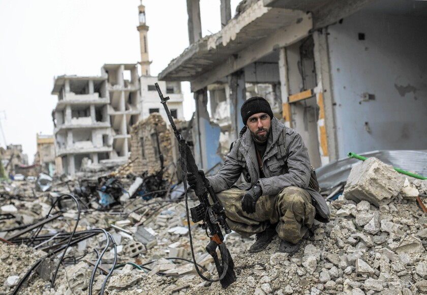 A Syrian Kurdish sniper sits on rubble in the city of Kobani. Last week, aided by U.S. airstrikes, the Kurds drove Islamic State extremists out of the city, which suffered tremendous damage.