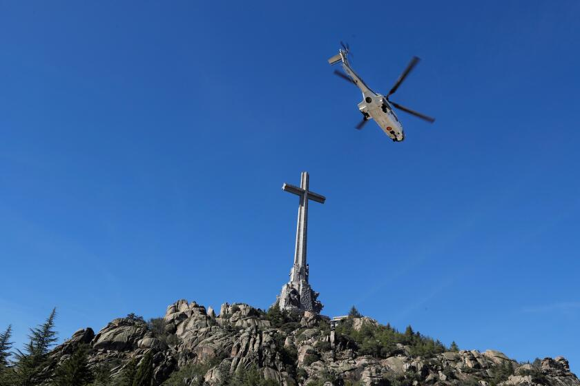A Spanish army helicopter carrying the remains of dictator Francisco Franco leaves the Valle de los Caidos (Valley of the Fallen) mausoleum Oct. 24 in San Lorenzo del Escorial.