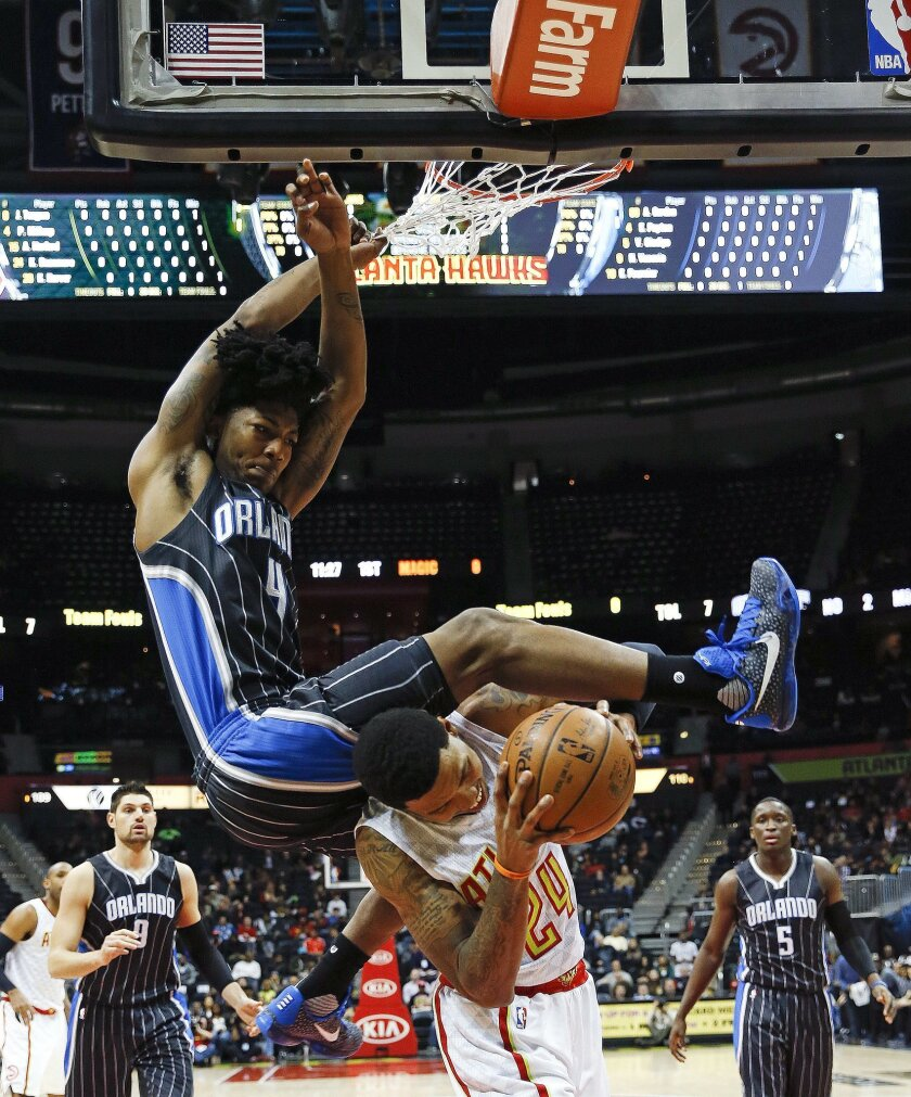 Atlanta Hawks forward Kent Bazemore (24) is fouled by Orlando Magic guard Elfrid Payton (4) as he goes up for a shot in the first half of an NBA basketball game Monday, Feb. 8, 2016, in Atlanta. (AP Photo/John Bazemore)