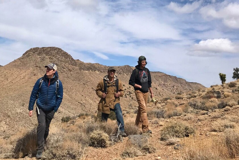 Three men walk in the Lone Pine area, where K2 Gold Corp. of Vancouver, Canada, is conducting exploratory drilling.