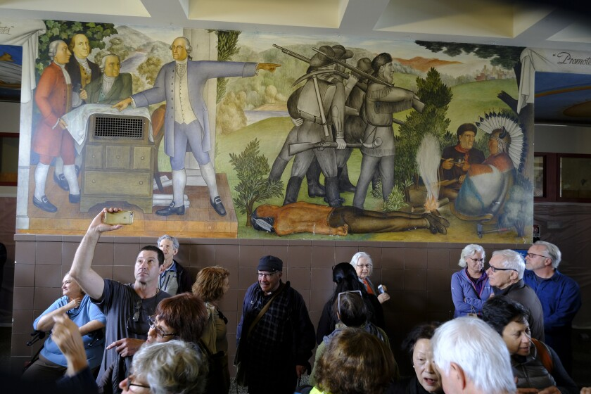 People gather in front of a mural depicting George Washington and other settlers and a dead Native American.