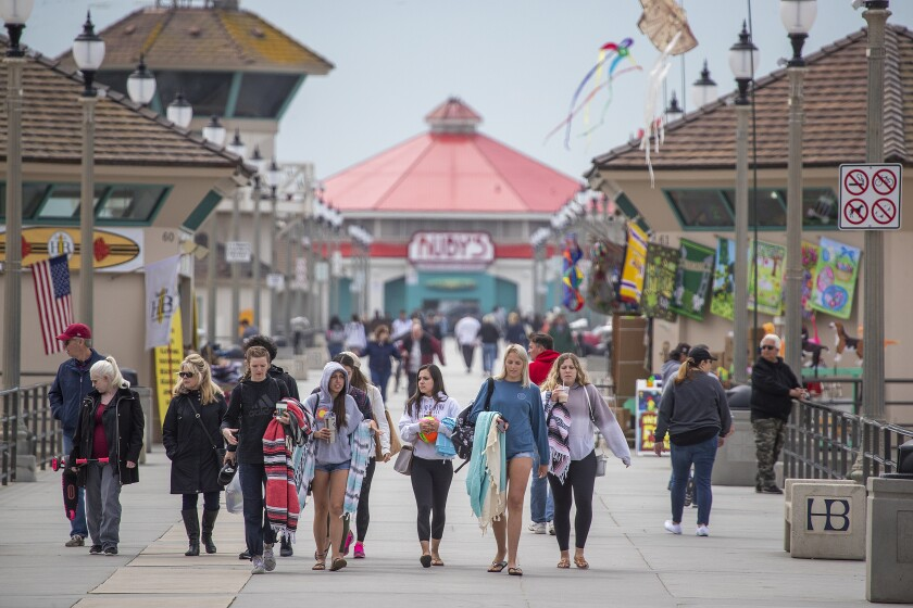 Spring breakers, visitors and locals walk on the pier amid coronavirus pandemic restrictions on Thursday in downtown Huntington Beach. Orange County bars, breweries and wineries were ordered to close, restaurants were told to offer take-out or delivery only, and people were told not to gather to curb transmission of the coronavirus.