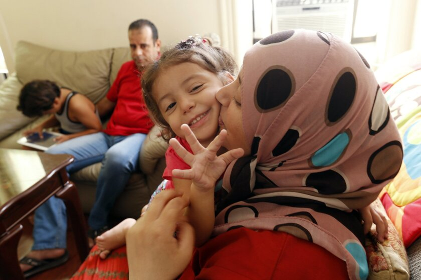 In this Wednesday, Sept. 16, 2015 photo, Maaesa Alroustom, center, is kissed by her mother, Suha, as her father, Hussam, back, sits with her brother Wesam in their apartment in Jersey City, N.J. The Alroustoms are Syrian refugees after fleeing their war stricken country. (AP Photo/Julio Cortez)