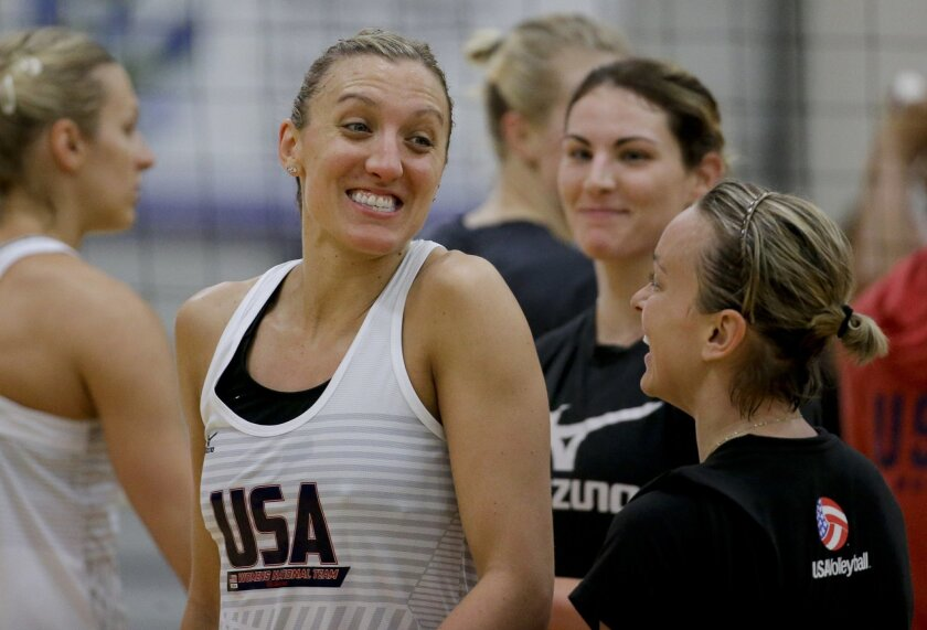 In this Tuesday, May 24, 2016, photo, Jordan larson, left, Kayla Banwarth, right, celebrate a point as Kelly Murphy looks during the U.S. women's national volleyball team practice in Anaheim, Calif. When the U.S. women's volleyball team got together months ago, the coaches embarked on a risky exper
