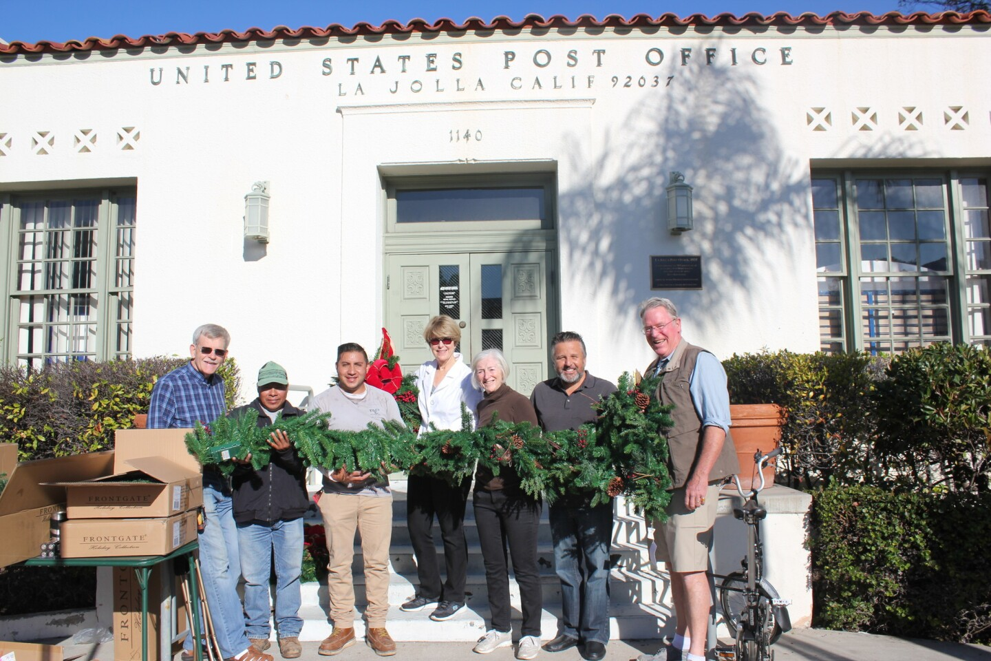 Volunteers Barry Bielinski, José Xinos, Israel Zea, Seonaid McArthur, Ann Craig, Raúl Albanez, John Peek hold the Christmas decorations for the La Jolla Post Office building.