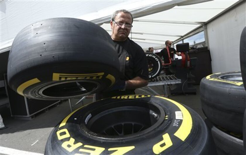 A Pirelli worker moves a tire at the Nuerburgring racetrack, in Nuerburg, Germany, Wednesday, July 4, 2013. The Formula One championship goes to this weekend's German Grand Prix on a bankrupt circuit amid concern over tire safety and with three-time champion Sebastian Vettel seeking his first win on home soil. The race at the Nuerburgring comes a week after a chaotic British Grand Prix in which five cars suffered tire blowouts, including that of leader Lewis Hamilton of Mercedes. Pirelli moved q