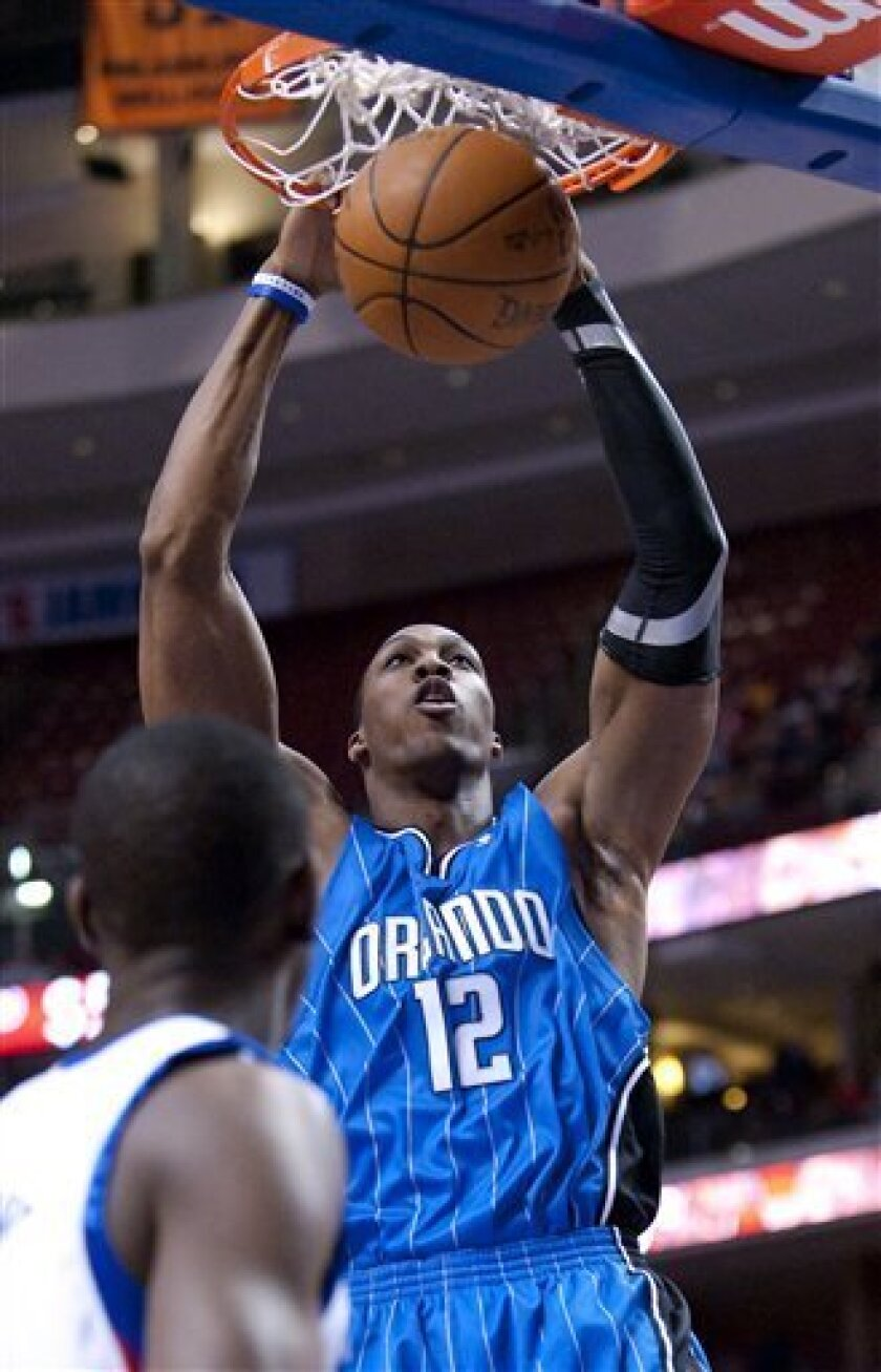 Orlando Magic center Dwight Howard dunks over Philadelphia 76ers guard Jrue Holiday in the first half of an NBA basketball game Monday, March 1, 2010, in Philadelphia. (AP Photo/Michael Perez)