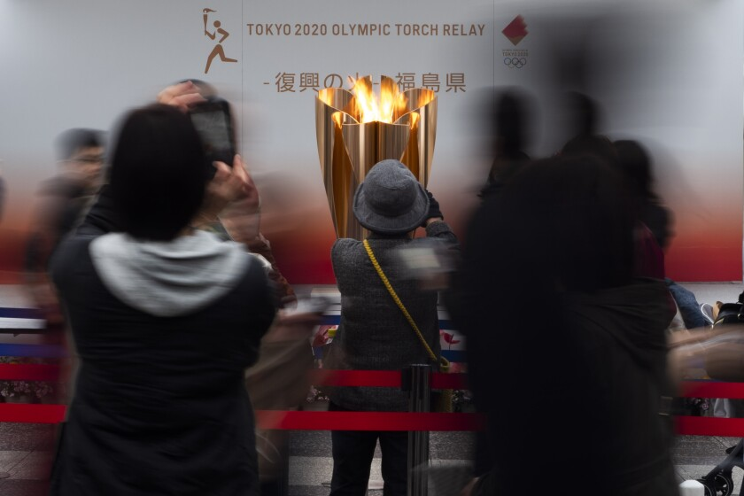 People take photos with their mobile phones of an Olympic flame display.