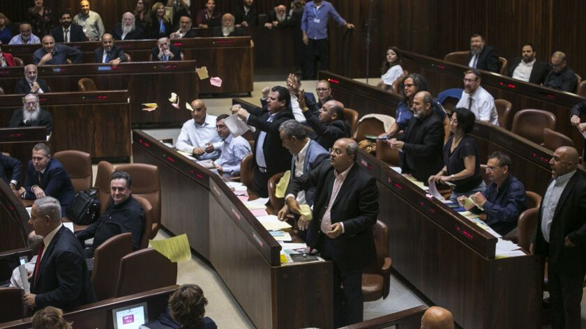 Arab lawmakers stand up in protest during a Knesset session in Jerusalem, Thursday, July 19, 2018. I