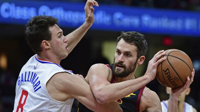 Clippers forward Danilo Gallinari tries to hold his ground as Cavaliers forward Kevin Love looks to score inside.