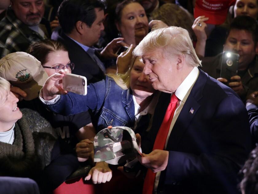 El precandidato presidencial republicano Donald Trump se toma fotografías con partidarios durante un acto de campaña, en Reno, Nevada. (Foto AP/Marcio José Sánchez)