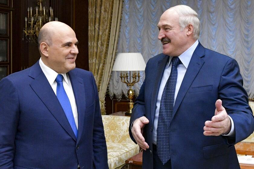 Belarusian President Alexander Lukashenko, right, gestures as he welcomes Russian Prime Minister Mikhail Mishustin for the talks in Minsk, Belarus, Friday, April 16, 2021. (Alexander Astafyev, Sputnik, Kremlin Pool Photo via AP)