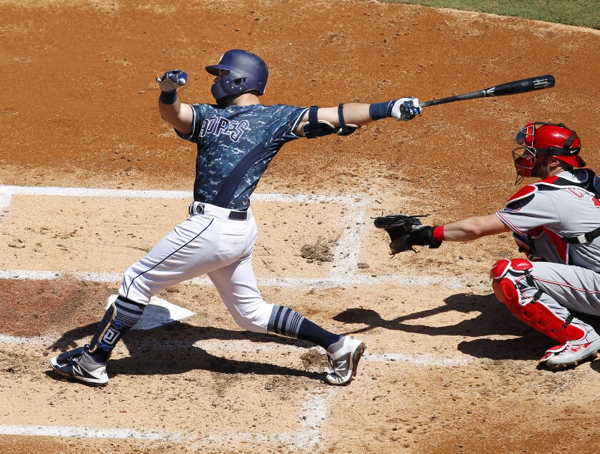 Padres catcher Austin Hedges hits a solo home run in the four-run third inning against the Reds on Sunday at Petco Park.
