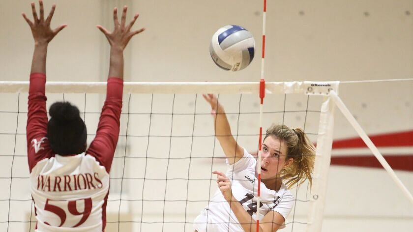 Laguna Beach High's Piper Naess puts a kill away past Mission Hills Alemany blocker Lindsey Felton d
