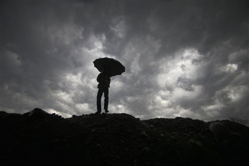 "FILE - In this Wednesday, March 9, 2011 picture, a boy walks with an umbrella to protect himself from the rain, as dark clouds hover over him in Jammu, India. If Earth overheats, can it be artificially cooled? Should the effort begin now? Who would decide? The very idea of ""geoengineering,"" and the unknown risks of tweaking our climate, left many participants in a March 2011 conference of international experts in Chicheley, England uneasy. (AP Photo/Channi Anand)"